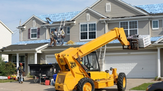 Three roofing contractors removing the old tiles before replacing with new shingles on a home