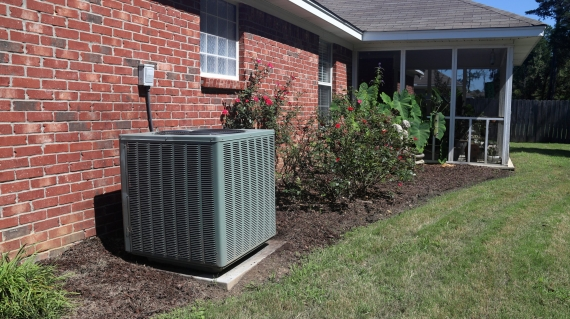 HVAC Air Conditioner system next to a home, modern clean with bushes and brick wall during the summer