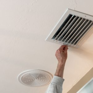 Handyman adjusting HVAC ceiling air vent. Air flow adjustment for overhead home heat and air conditioning ventilation duct.