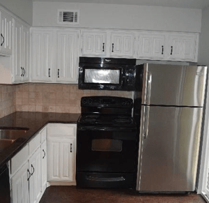 a kitchen with with stainless steel fridge, black stove and a black over the range microwave. White cabinets and black countertops. Kitchen receiving maintenance and being cleared.