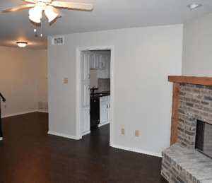 Empty rooms with clean wood floors a fireplace receiving maintenance. Room has white walls and a white ceiling fan with three lights turned on. Empty room maintenance managing tenant vacancy
