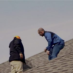 two classic construction GAF master elite certified contractors on the roof examining roof material