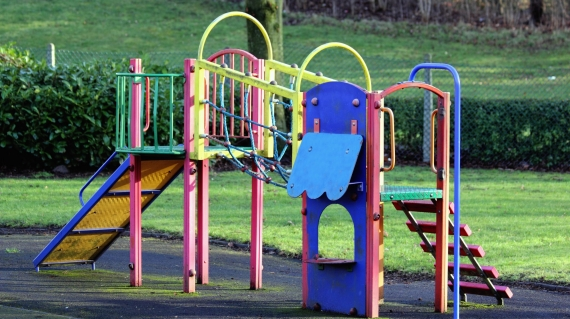 Playground slide and stairs with various primary colored railing.