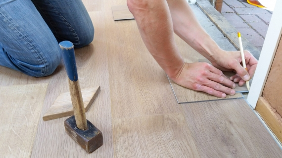Man repairing wood floor with a hammer his right and a pencil in his hand.