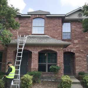 heat damage to Texas home going through inspection with brick layer, Classic Construction employee standing next to a ladder outside of the home