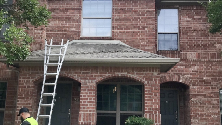 Classic Construction employee standing next to a ladder outside of a brick Texas home which is going through a roof inspection due to heat damage.