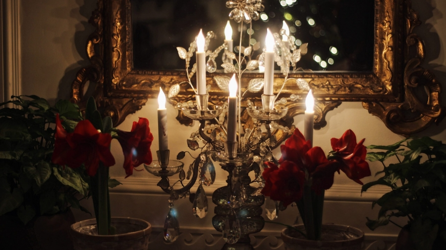 holiday lamp with candles that are lit close to a mirror.