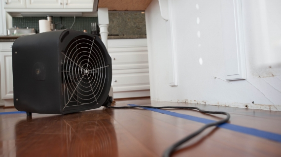 Kitchen island affected by water damage is being dried using a strong powered fan.