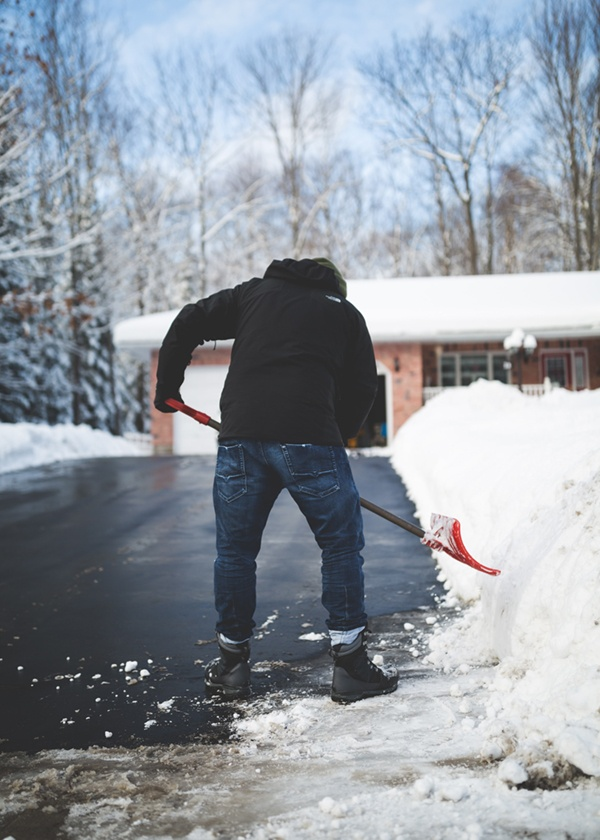 shoveling snow near an icy driveway